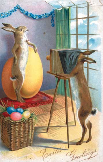 A rabbit posing with a giant Easter egg while another rabbit takes his picture